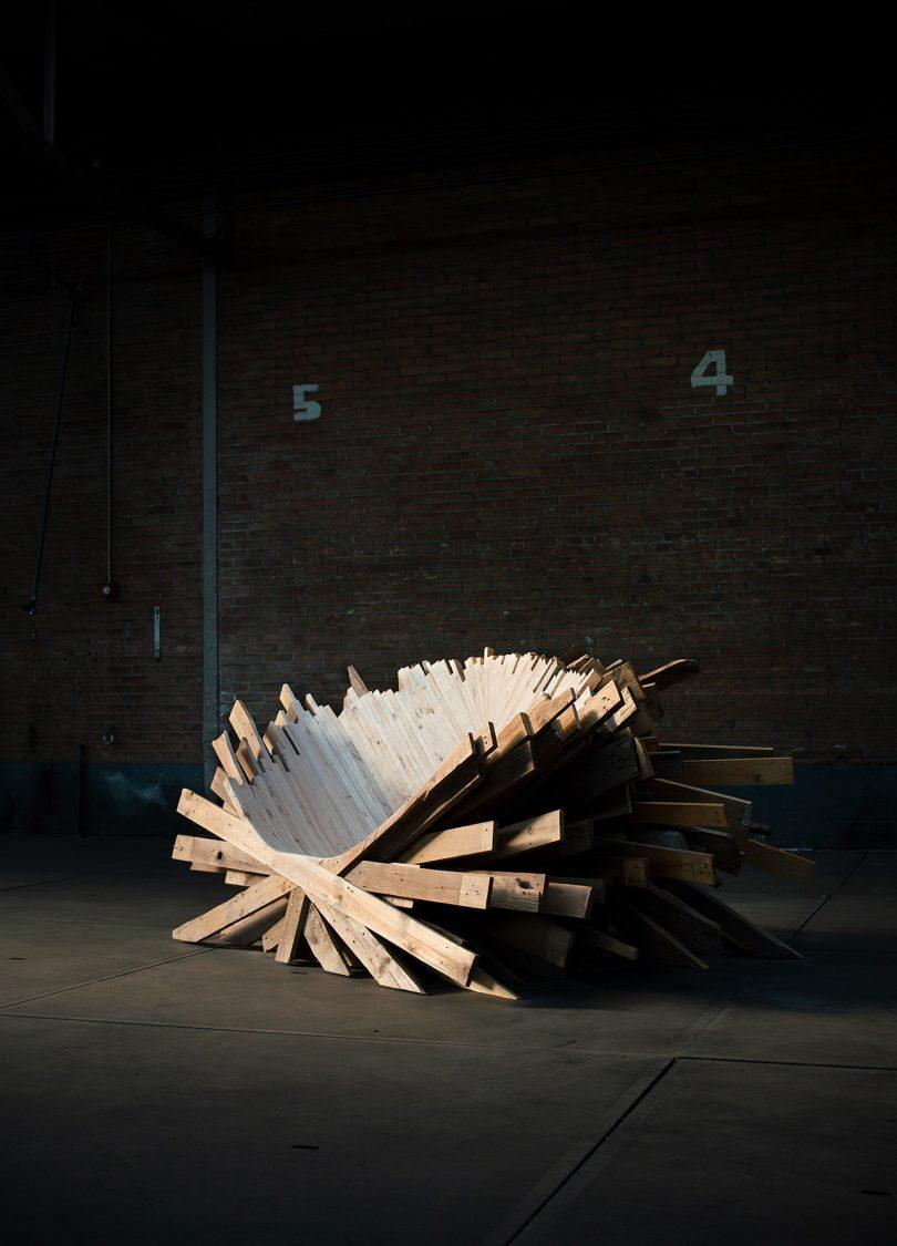 wooden sculpture displayed in dark space