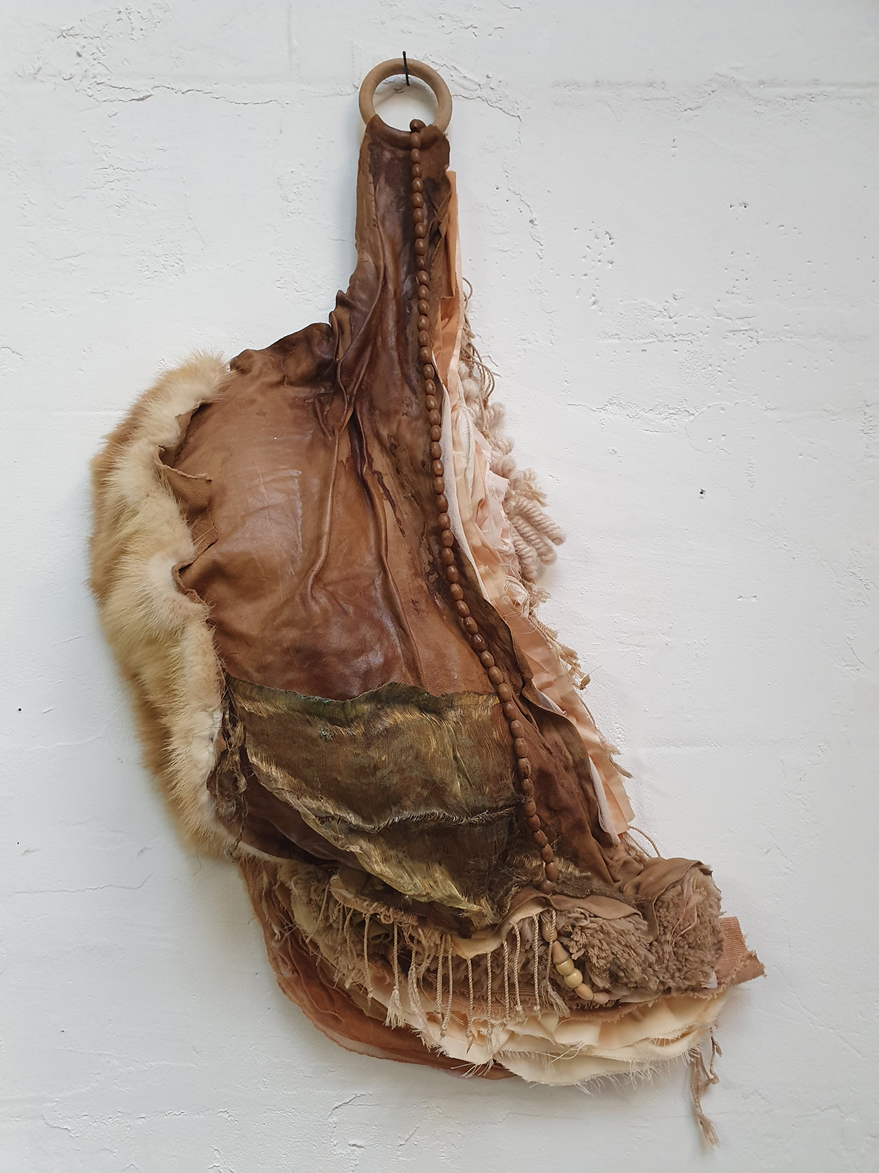 brown textile art hanging on white wall