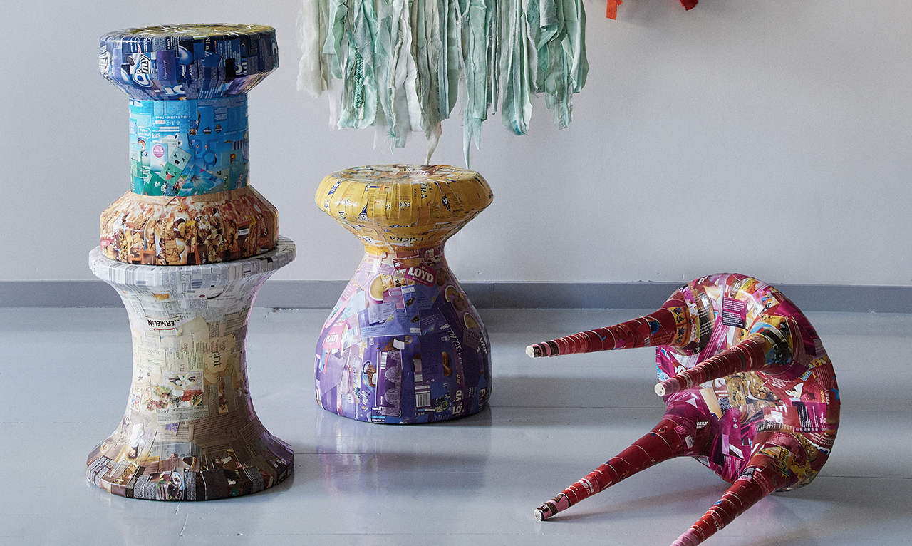 colorful textile art and functional objects displayed on wall and floor