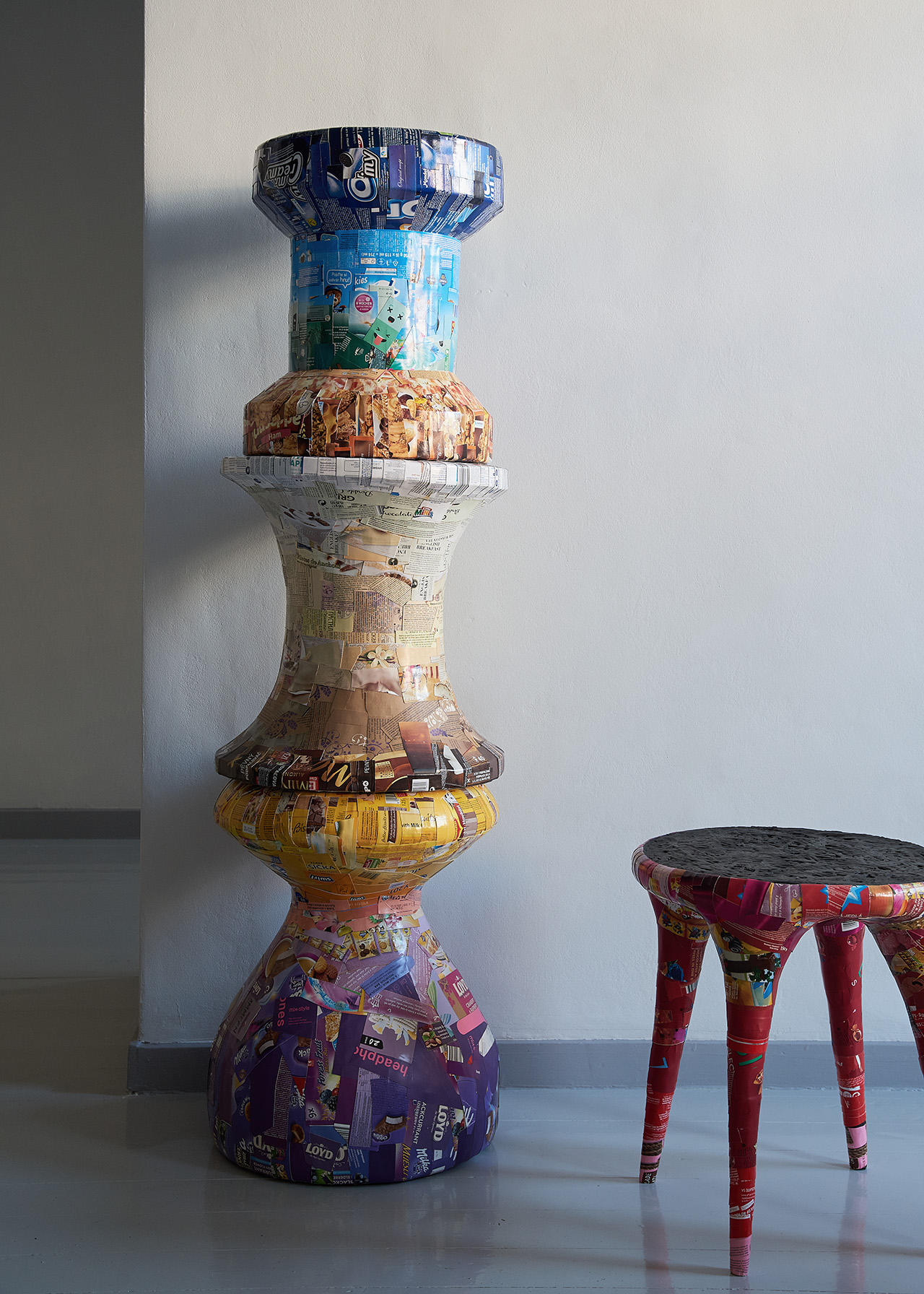 three stacked collaged stools and one lone stool in interior space