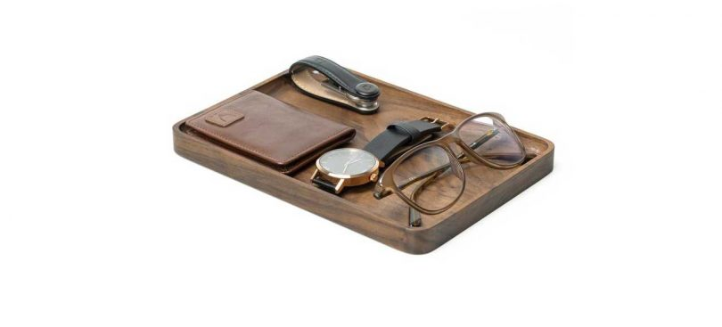 modern wood tray holding essentials, like watch, glasses and wallet