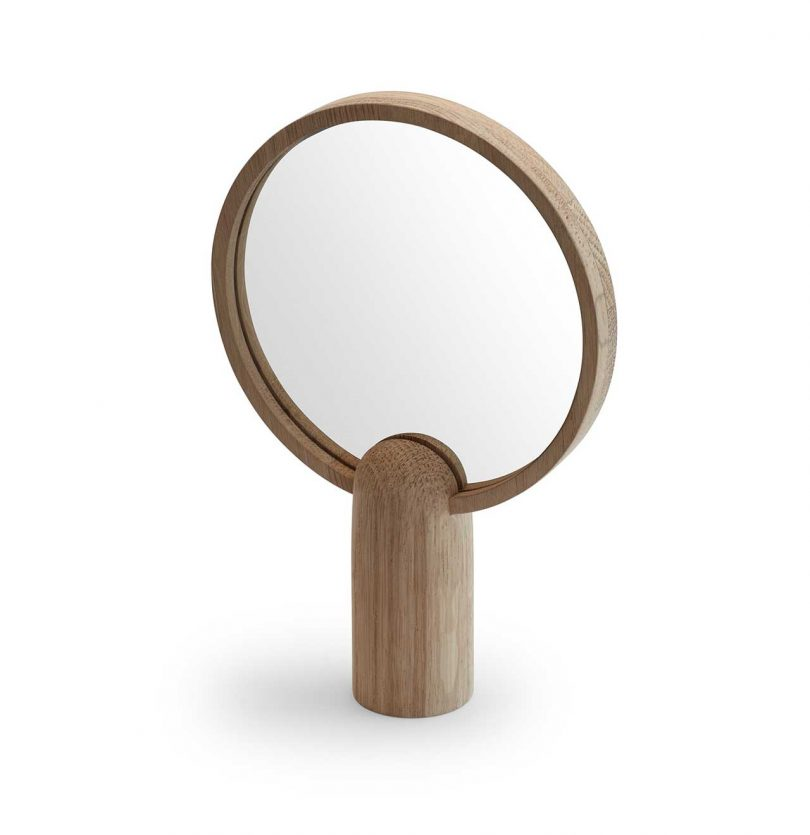 wood framed round mirror atop a wood base