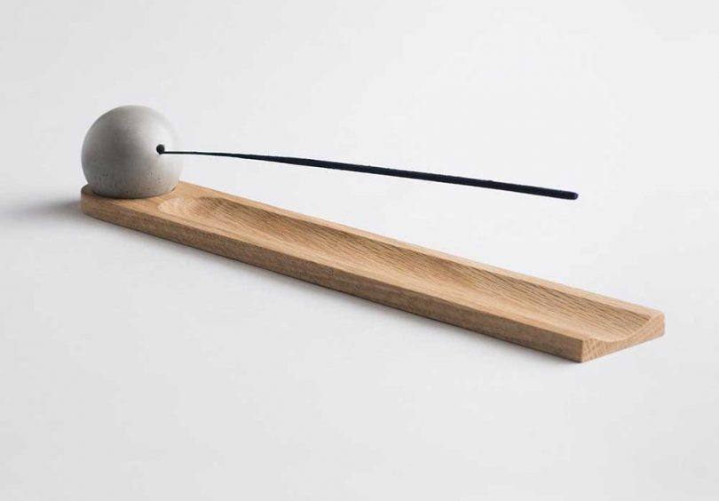 modern incense burner with wood base and concrete sphere holding the incense stick