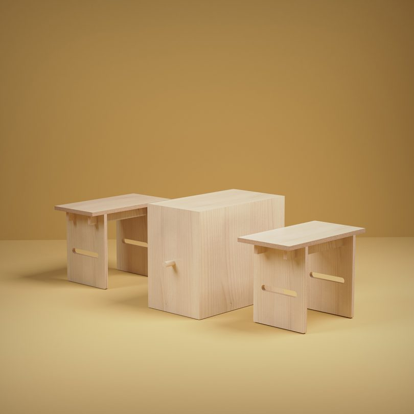 unfinished wood table and two stools on golden yellow background
