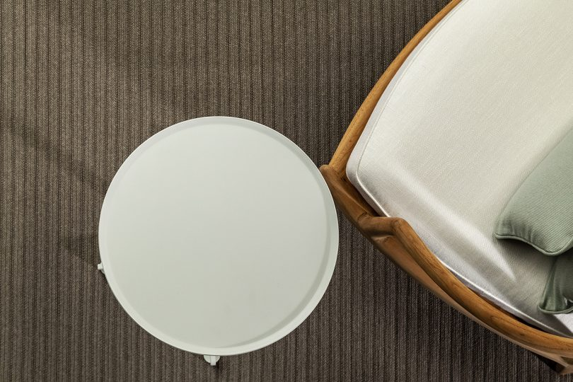 overhead photo of round white table, chair with white cushion, and grey rug