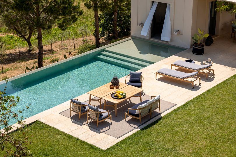 pool with patio full of outdoor furniture overlooking the countryside