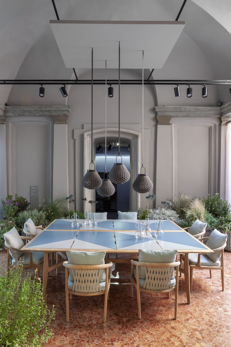 outdoor dining tables with eight armchairs and four lighting pendants inside a light colored space