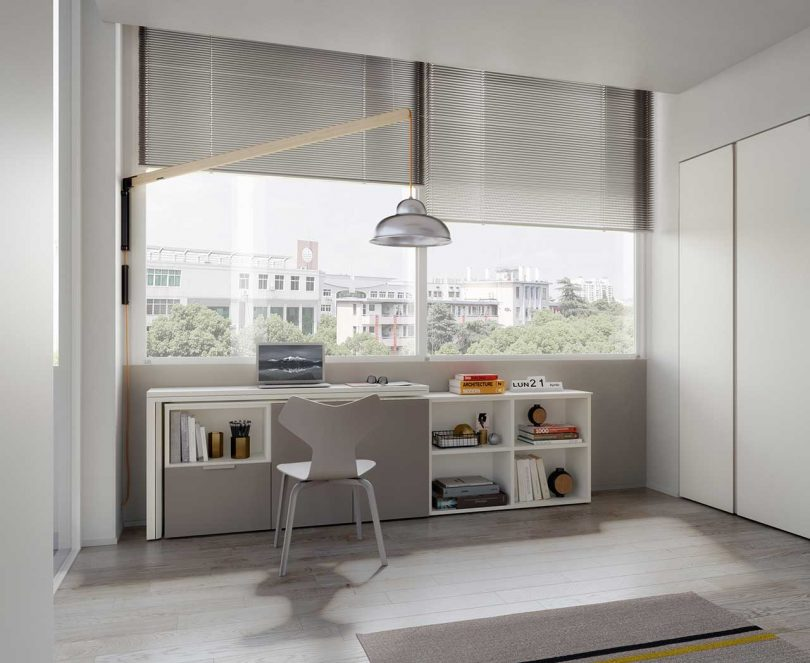 interior room with low white bookshelf doubling as a desk in front of windows