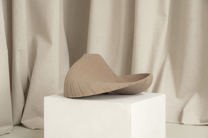 light brown abstract vessel sitting on white pedestal in front of light fabric