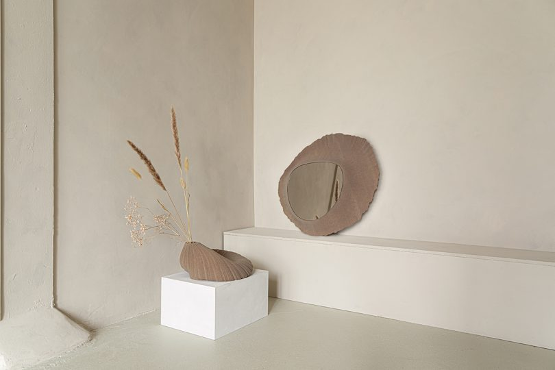 light brown abstract vessel sitting on white pedestal and light brown mirror sitting on a ledge leaning against light wall
