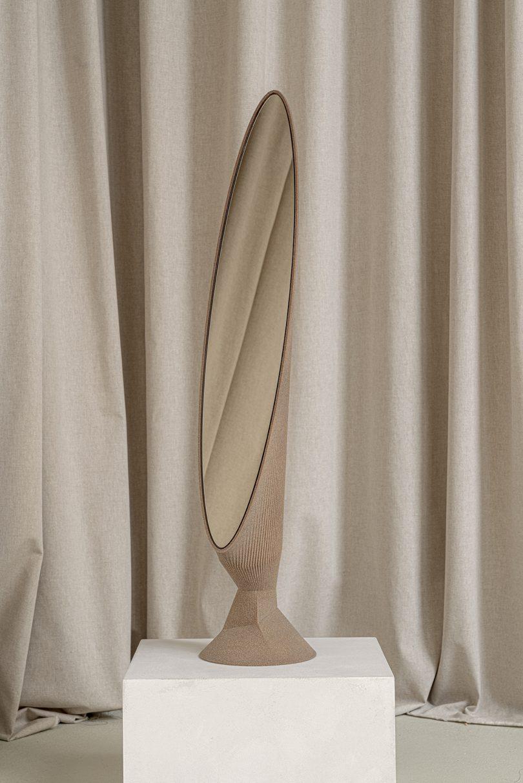light brown oblong floor mirror on white pedestal in front of light fabric
