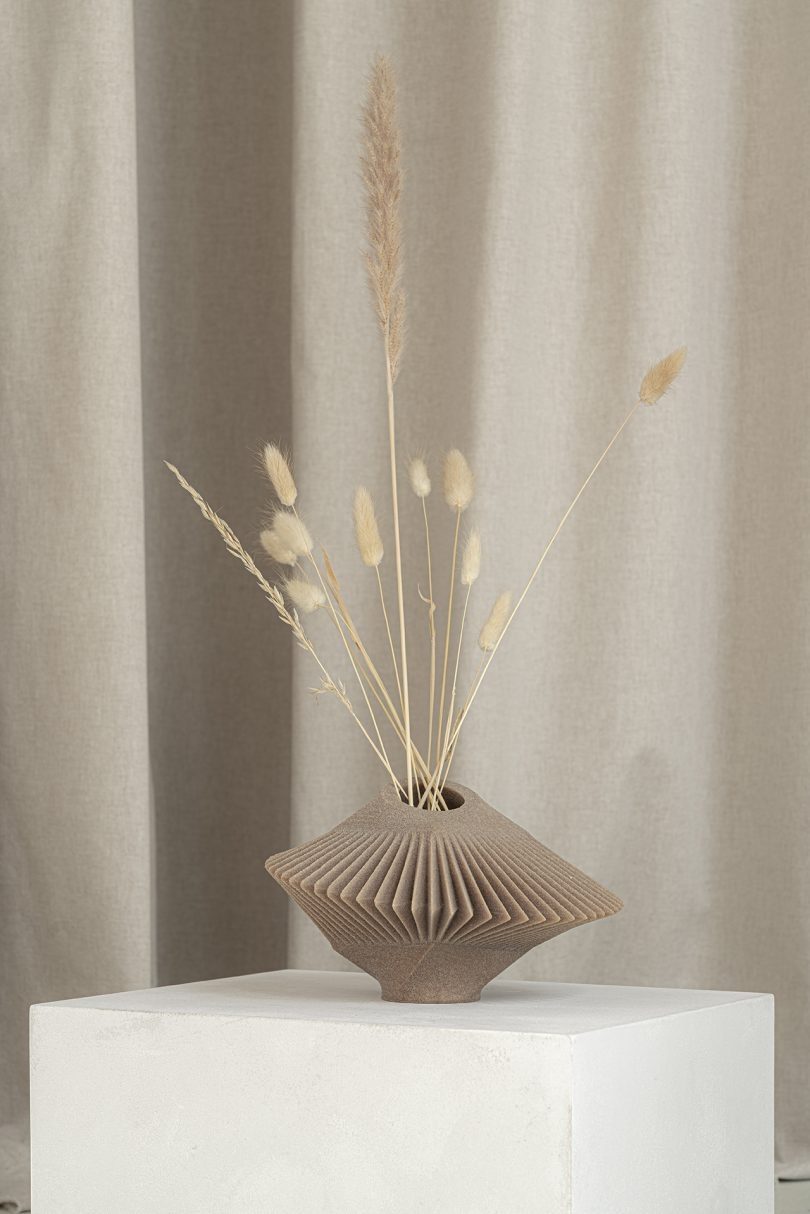 light brown abstract vessel with dried stems sitting on white pedestal in front of light fabric
