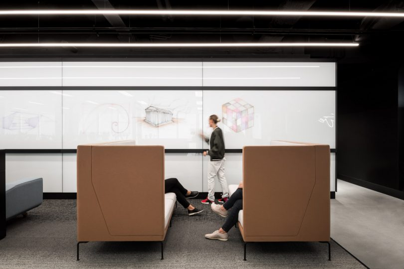 individual giving presentation on white board while others sit in booths opposite one another