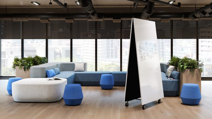 double-sided whiteboard in a room of modern office furniture in front of a wall of windows