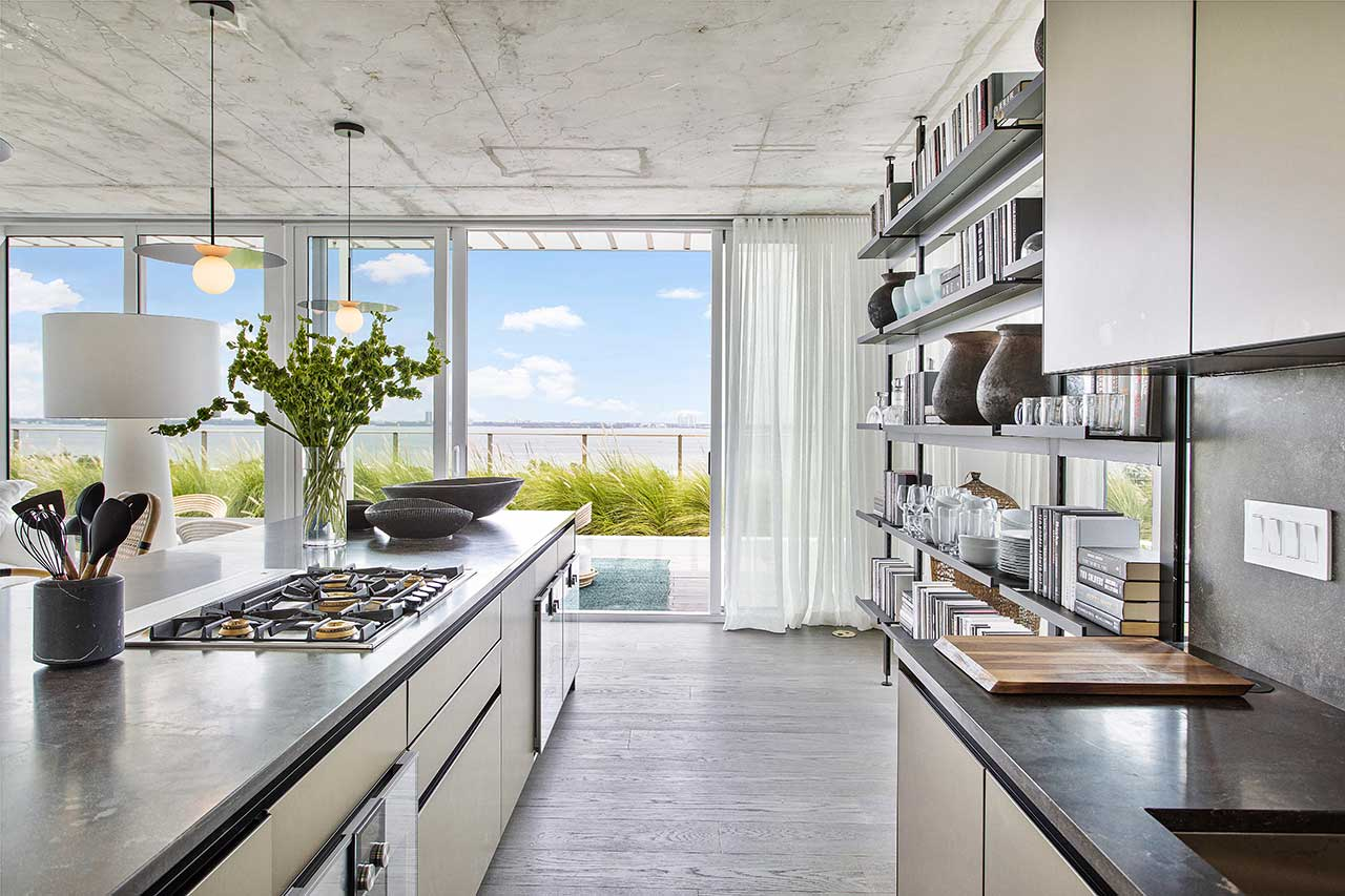 modern kitchen in neutral colors with open shelving in front of window