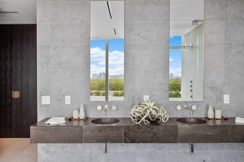 modern minimalist bathroom with dark wood floating vanity and gray stone surfaces