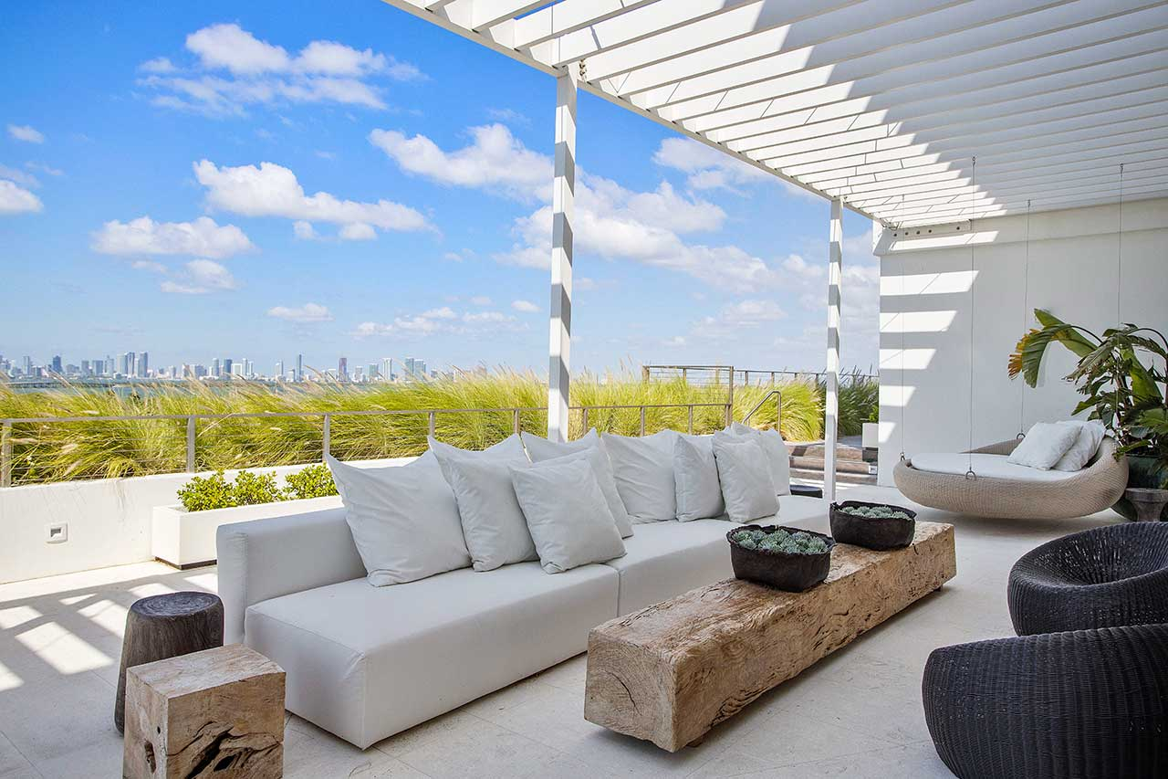 covered patio in penthouse with white sofa overlooking city