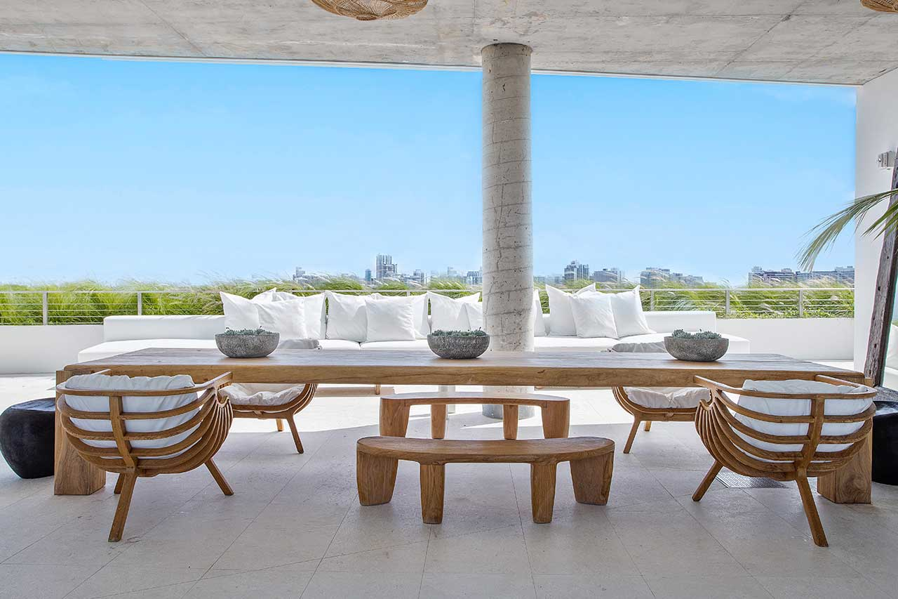 covered patio on rooftop with wooden dining set and white sofa