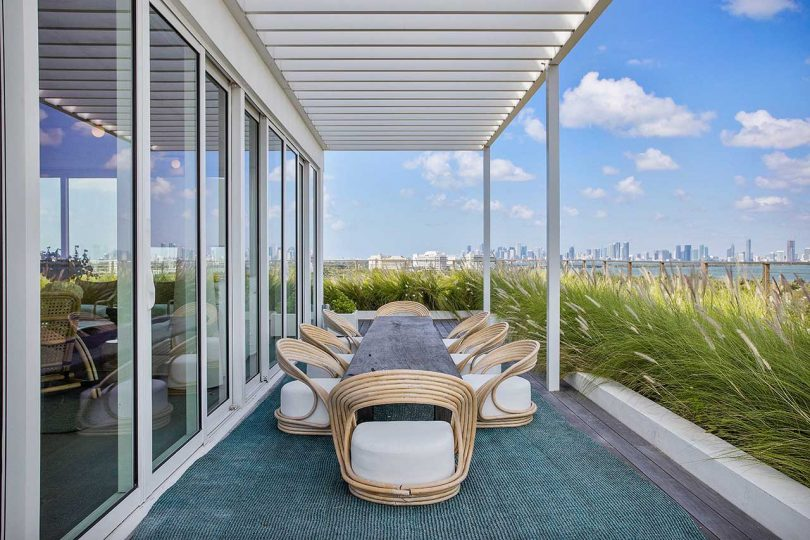 wooden dining set under pergola on penthouse rooftop