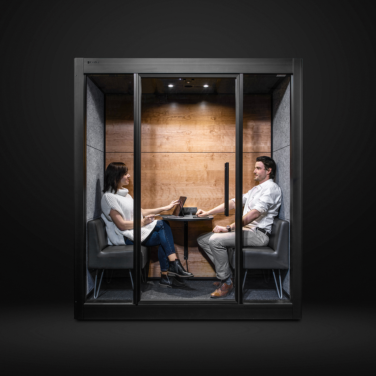 workspace pod with two people inside on dark background