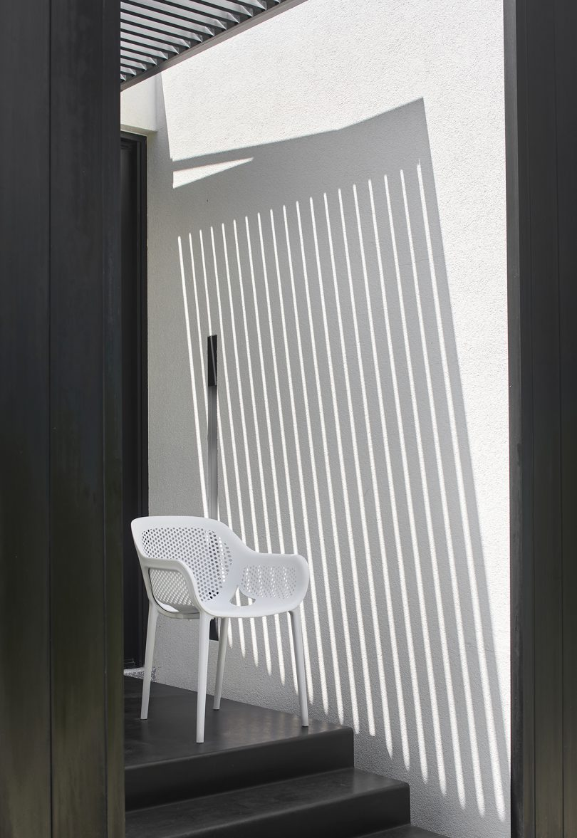 white outdoor armchair next to white slatted architectural feature