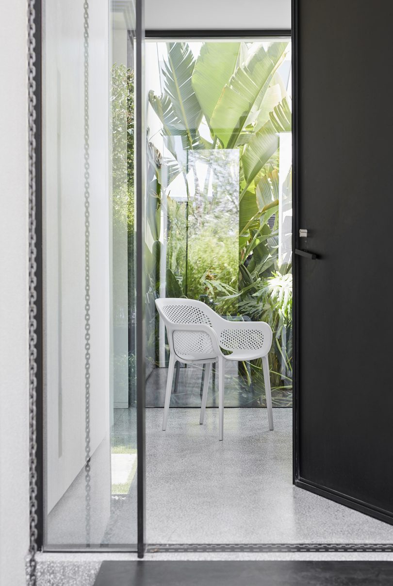 white outdoor armchair seen on patio through a window