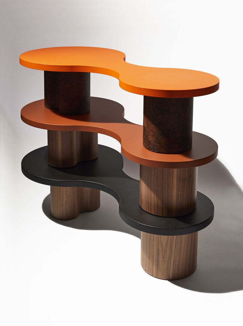 three stacked coffee tables in orange, umber, and black