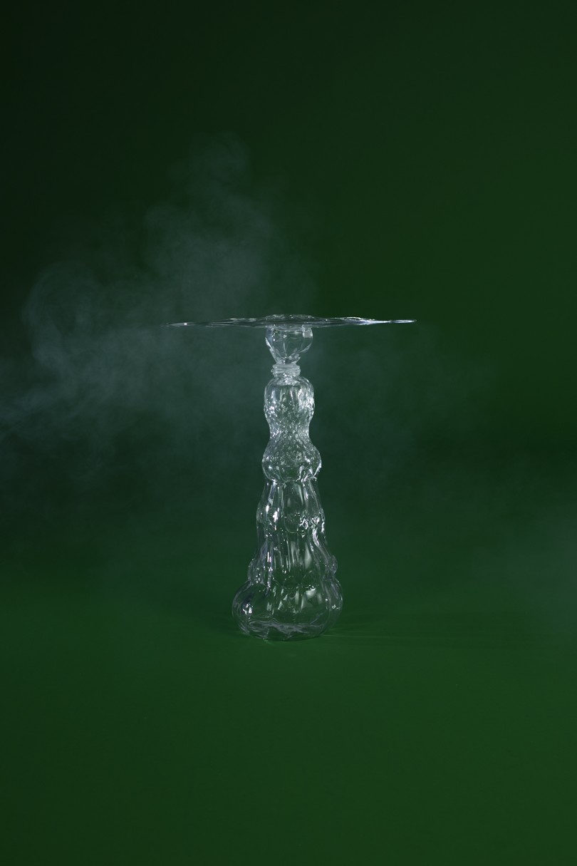 glass side table on dark green background