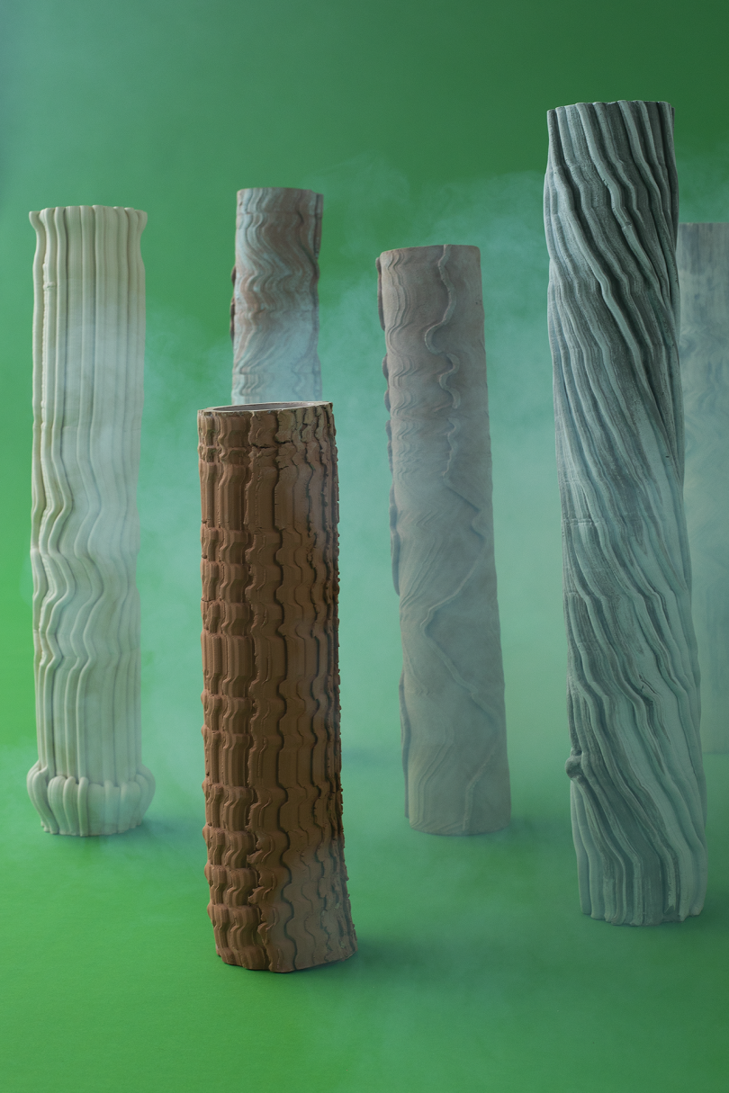 pillars of varying colors and heights on green background with white smoke