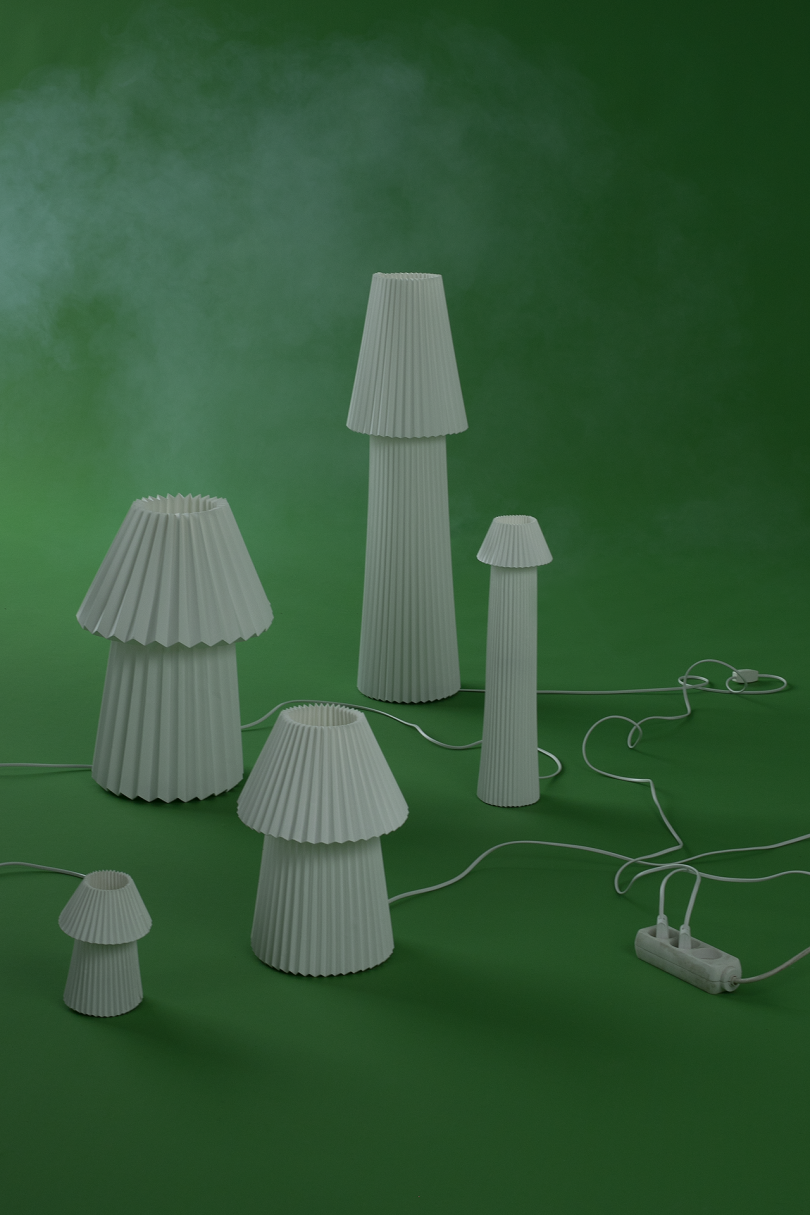 collection of white mushroom shaped lamps on green background with white smoke