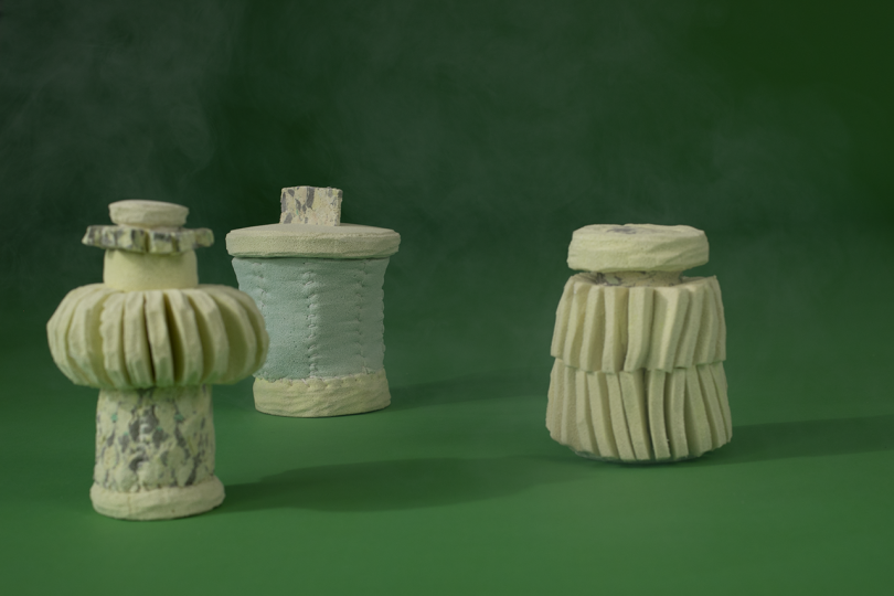 three light colored containers on dark green background