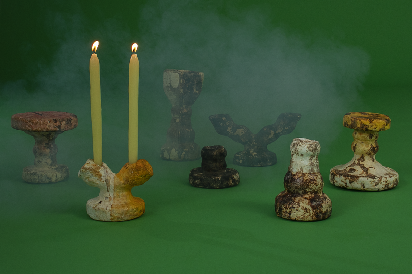 collection of vessels with two lit candles on dark green background with white smoke
