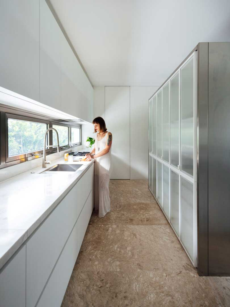 modern galley kitchen with white cabinets and windows as backsplash