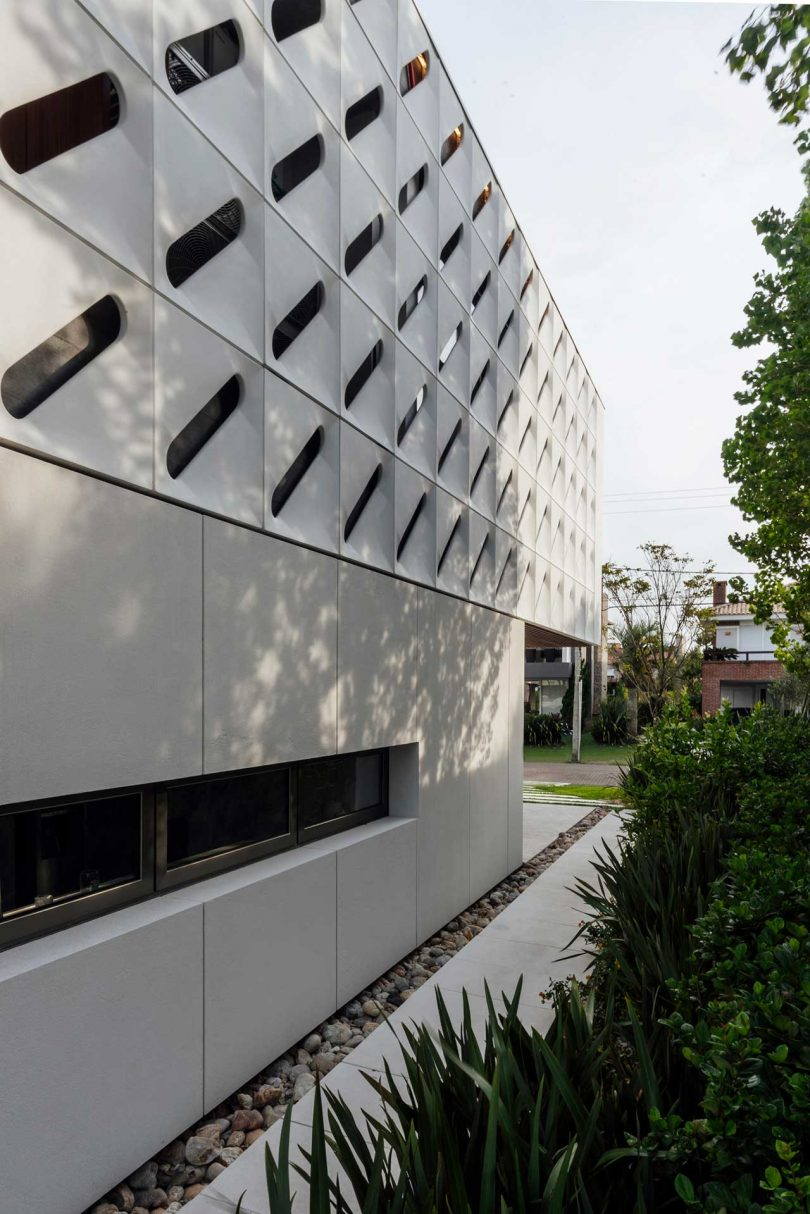 walkway by side of modern white house with diagonally slotted facade