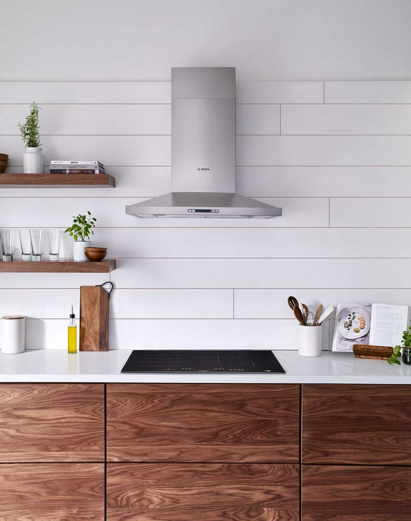 modern kitchen closeup of wooden cabinets, white tile backsplash and stainless steel hood
