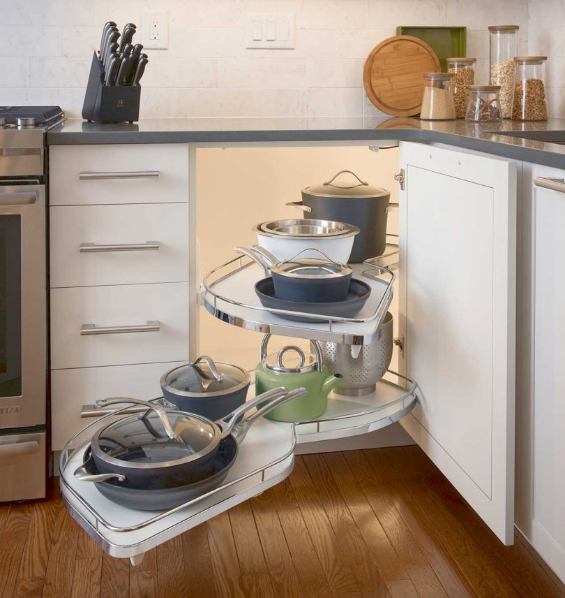 kitchen cabinet with lazy susan out holding pots and pans