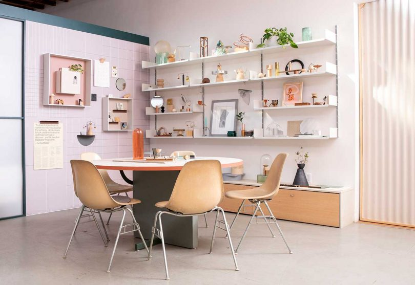 modern workspace with shelves holding trinkets and a table with chairs