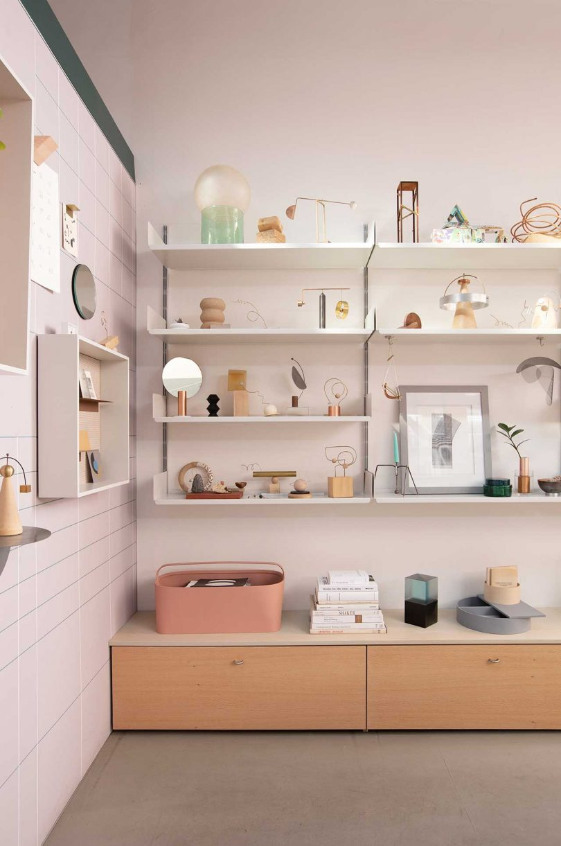 office with pink walls and shelves with design objects and art