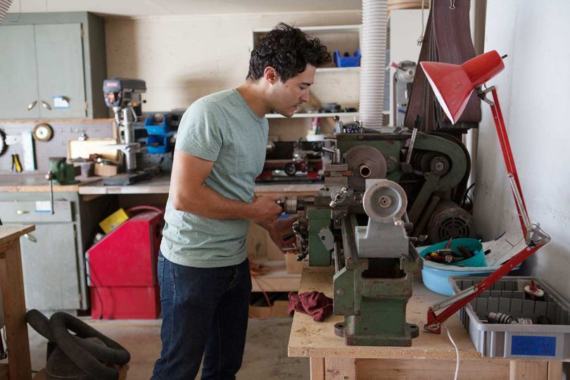 man working in woodshop on a power tool