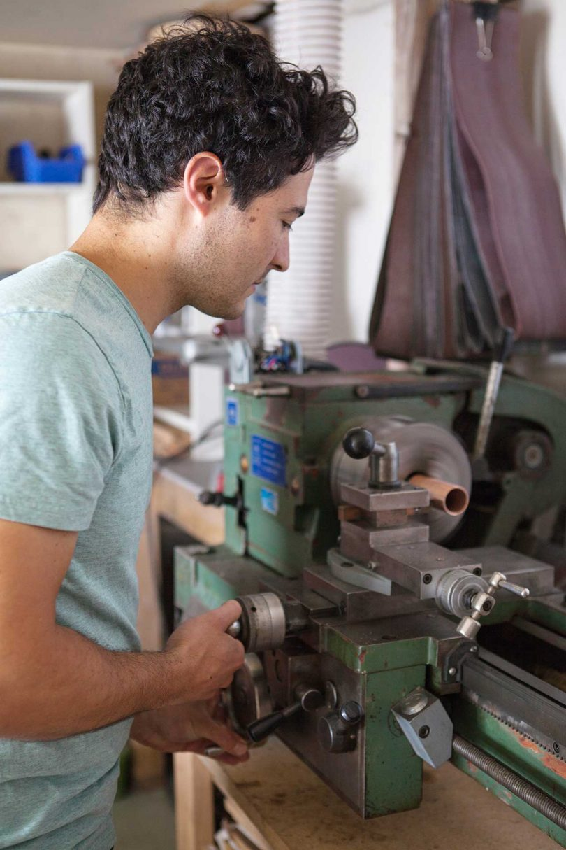 man working on lathe in tool shop