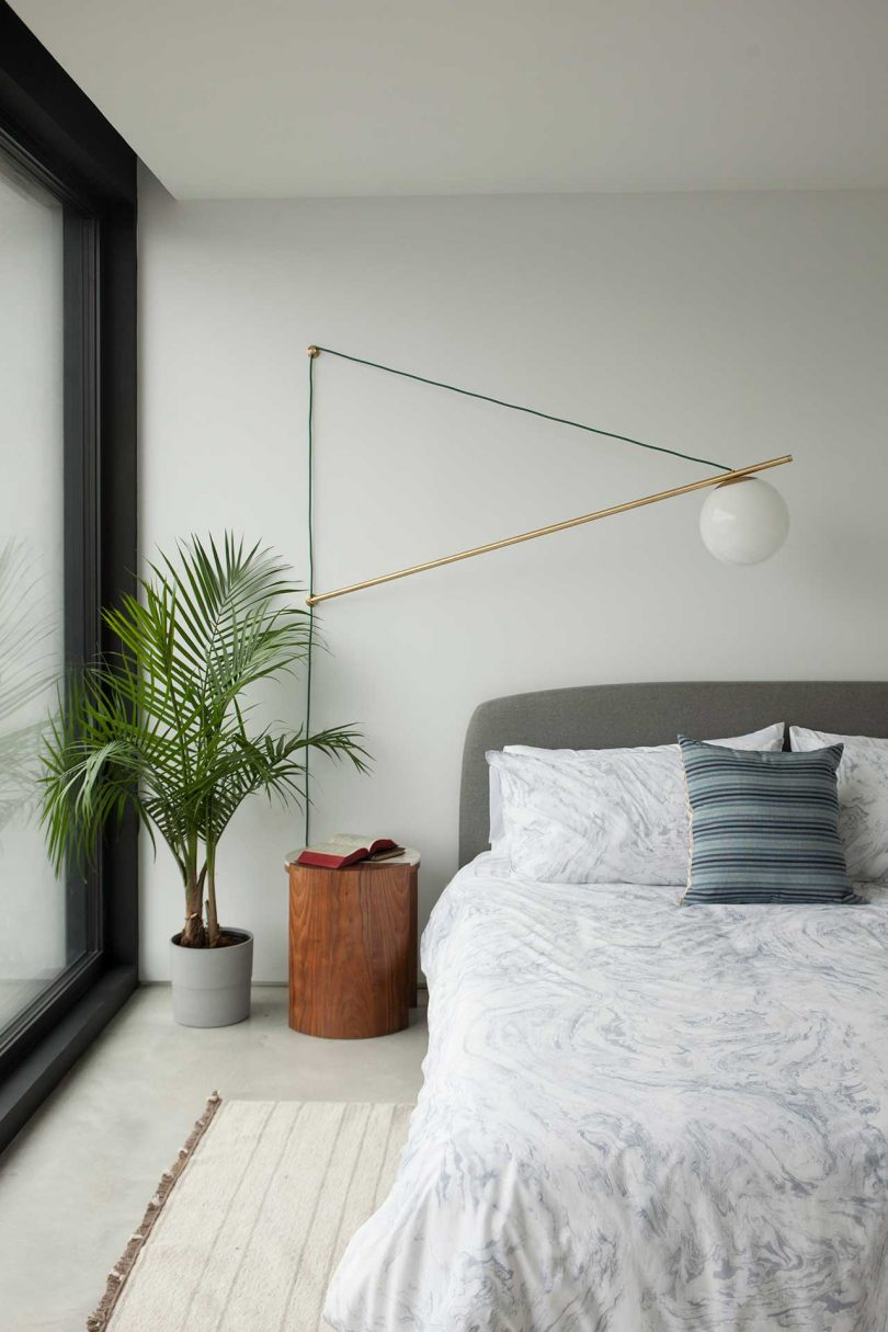 view of half of a bed with light bedding and geometric lamp