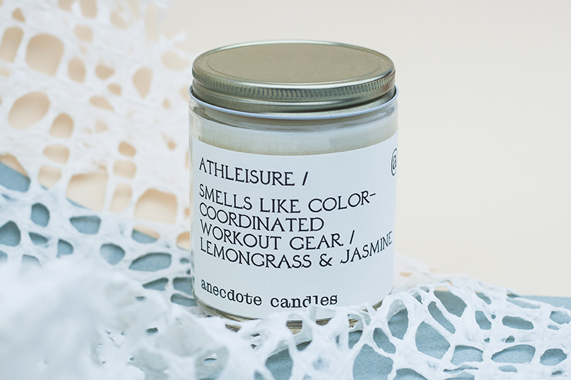 athleisure candle by anecdote candles on a light beige background with artsy texture underneath