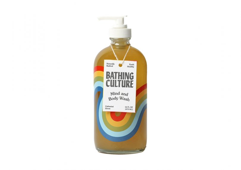 Bathing Culture Mind + Body Wash in glass rainbow bottle with white pump on a white background