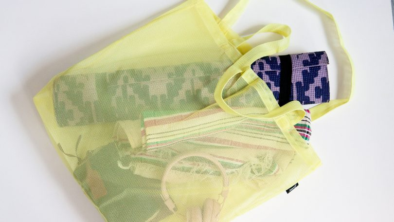 a yellow junes grande bag with a yoga mat and other essentials inside