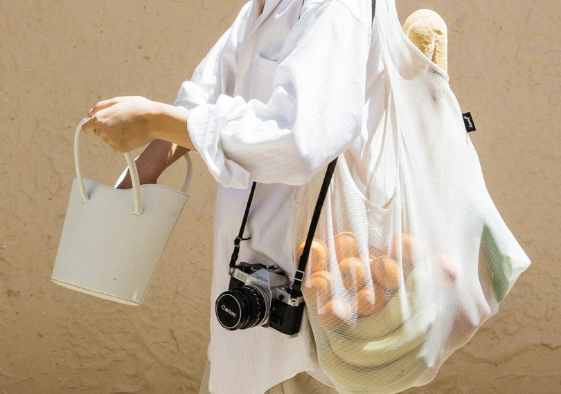 person carrying a white junes everyday tote over their shoulder with produce and other things inside