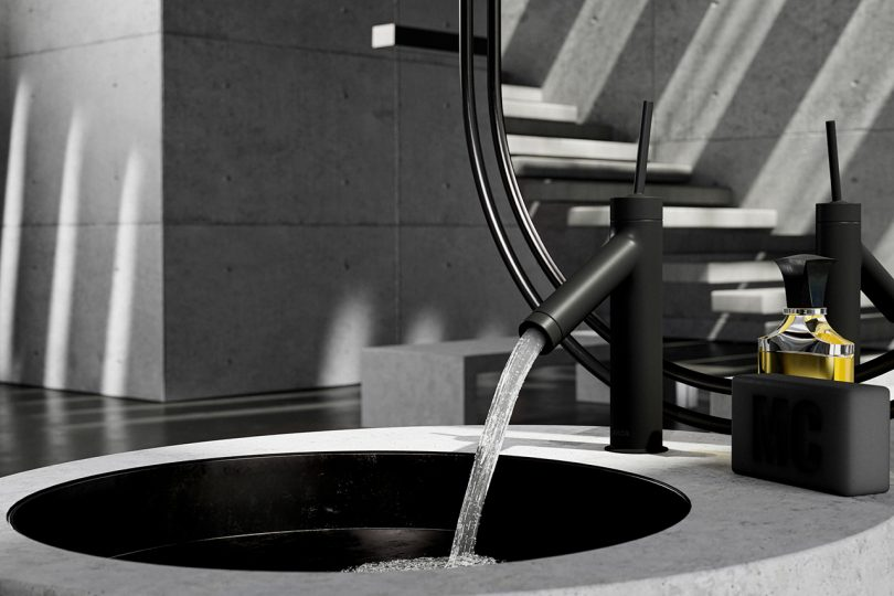 sleek black bathroom faucet turned on and flowing into a stone sink