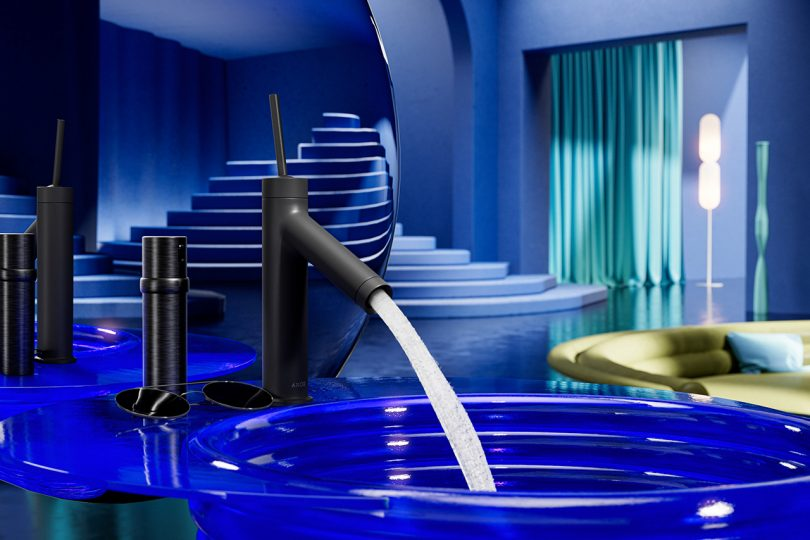 sleek black bathroom faucet turned on and flowing into a blue glass sink