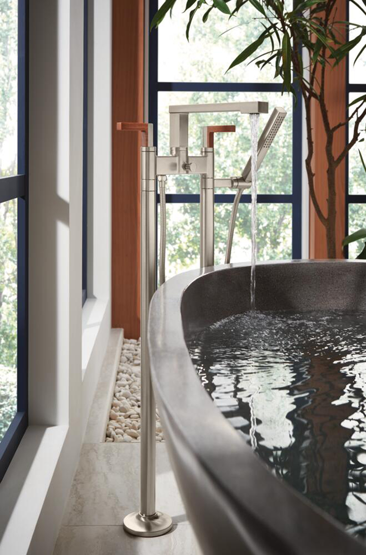 corner of dark grey bathtub with metal rub filler surrounded by windows