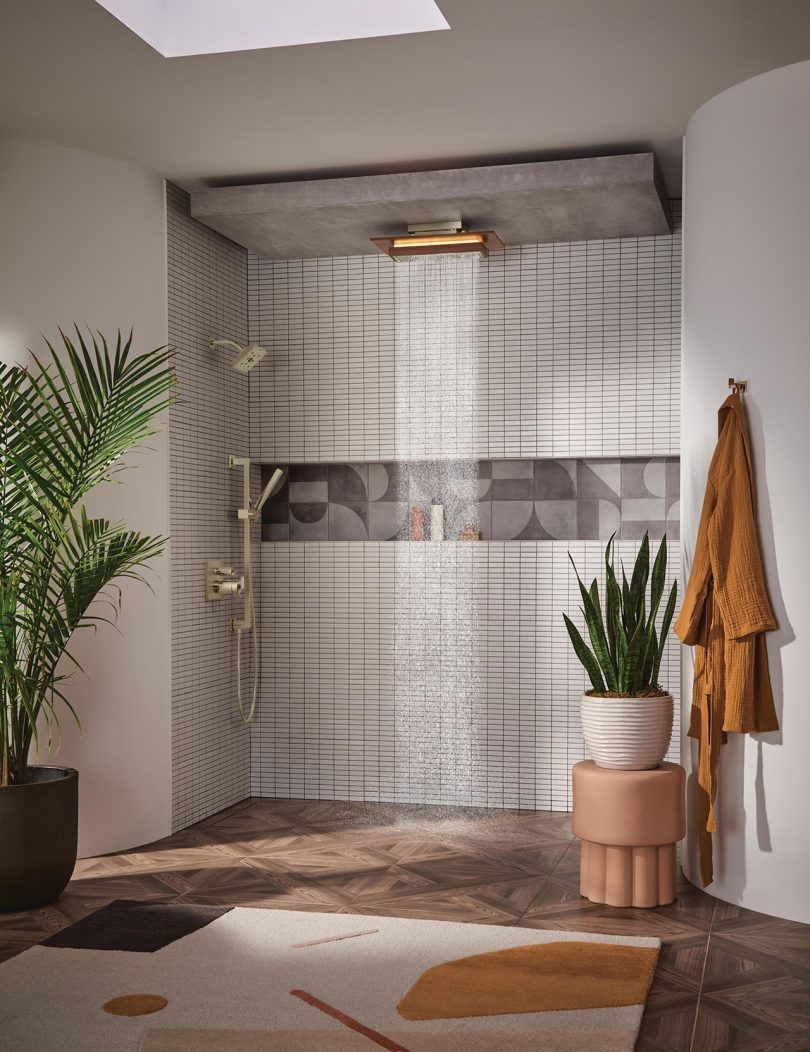 canopy showerhead in open tile shower with two plants, a stool, and a hanging robe