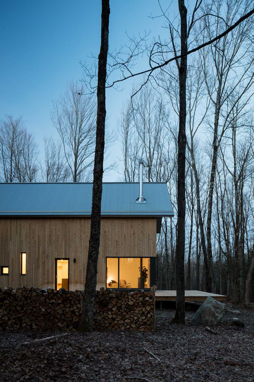 modern wood cabin in the woods at twilight